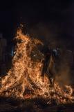 En man som rider hans hästbanhoppningthroug branden Arkivbilder