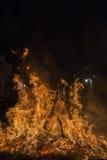 En man som rider hans hästbanhoppningthroug branden Arkivbild