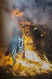 En man som rider hans hästbanhoppningthroug branden Arkivfoton