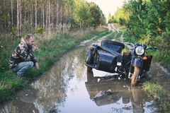 En man som rider en motorcykel med en sidecar, fick fastnad på vägen i skog Arkivbild