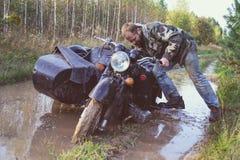 En man som rider en motorcykel med en sidecar, fick fastnad på vägen i skog Royaltyfri Foto
