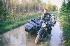En man som rider en motorcykel med en sidecar, fick fastnad på vägen i skog Fotografering för Bildbyråer
