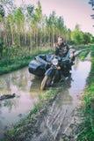 En man som rider en motorcykel med en sidecar, fick fastnad på vägen i skog Arkivfoton