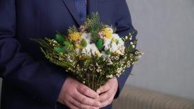 En man som rymmer en bukett av h?rliga blommor lager videofilmer