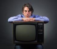 En man som rymmer en retro television Arkivbilder