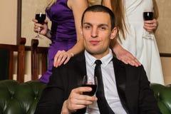 En man som rymmer ett exponeringsglas av vin Royaltyfri Bild