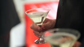 En man som rymmer ett exponeringsglas av vitt vin, closeup stock video