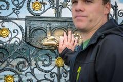 En man som rymmer hans hand mot en dekorativ bronsplatta på ett staket i Prague fotografering för bildbyråer