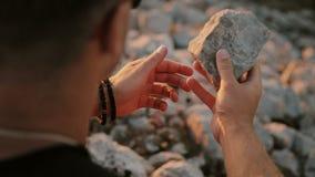 En man som rymmer en sten i hans handcloseup lager videofilmer