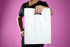 En man som rymmer en vit plastpåse close upp Isolerat på rosa bakgrund arkivfoton