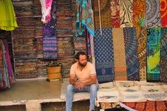 En man som säljer färgrika sarees i hans, shoppar royaltyfri foto