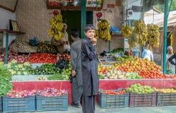 En man som säljer frukter och grönsaker till en kund på en speceriaffär royaltyfri bild
