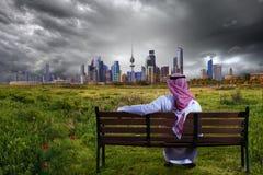 En man som ser staden från en trädgård Royaltyfri Bild