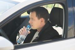 En man som sitter bak hjulet av en bil och ett dricksvatten från en plast- flaska fotografering för bildbyråer