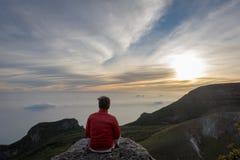 En man som sitter och tycker om soluppgång på, vaggar upptill av Gede Pangrango Mountain arkivfoton