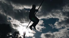 En man som sitter på ett rep som hoppar över jordningen Kontur mot himlen Kall l?ngd i fot r?knat stock video
