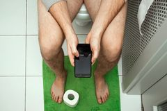 En man som sitter på toaletten som rymmer en smartphone i hans händer, bästa sikt Begreppet av problem med stolen, inälvor, fotografering för bildbyråer