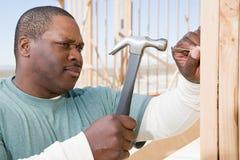 En man som slår en spika med en hammare arkivbilder