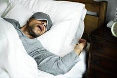 En man som sover på en säng arkivfoto