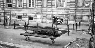 En man som sover på en träbänk i gatorna av Paris, Frankrike royaltyfria bilder