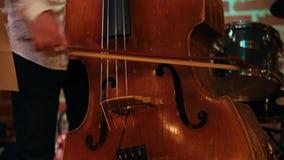 En man som spelar en basfiol i en jazzstång, endast hans händer, är synlig lager videofilmer