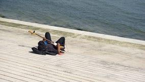 En man som spelar gitarren på stranden i Lissabon royaltyfri foto