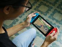 En man som spelar Mario Kart 8 som är lyx- på den Nintendo strömbrytaren Arkivfoton