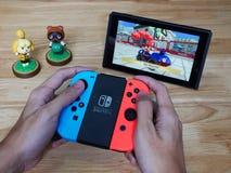 En man som spelar Mario Kart 8 som är lyx- på den Nintendo strömbrytaren Arkivfoto