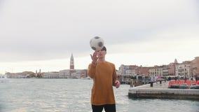 En man som spelar med en fotbollboll p? st?llningen p? en bakgrund av havet Rotering av bollen p? hans finger stock video