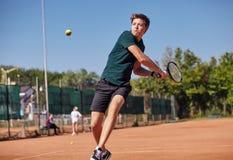 En man som spelar tennis på domstolen på en härlig solig dag arkivbild