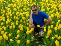 En man som squatting ner framme av en guling och en röd tulpangardrn arkivbilder