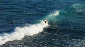 En man som surfar på den vita skumvågen i det blåa havet med folkswimm Royaltyfria Foton