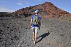En man som trekking i den vulkaniska Timanfaya nationalparken Arkivbild