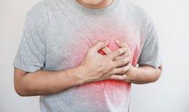 En man som trycker på hans hjärta, med röd viktig av hjärtinfarkt, hjärtafel, andra hjärtsjukdom och bruten hjärta royaltyfri fotografi