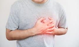 En man som trycker på hans hjärta, med röd viktig av hjärtinfarkt och andra hjärtsjukdombegrepp, på vit bakgrund fotografering för bildbyråer