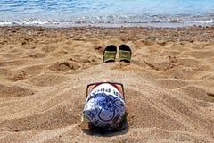 En man som vilar på kusten som begravas i varm sand arkivbilder