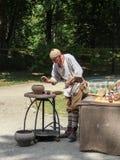 En man som visar gamla keramikerhantverk arkivbild