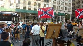 En man som visar med förbundsmedlemflaggor i New York City Arkivfoton