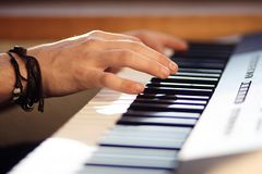 En man spelar en melodi på en modern musikalisk synt royaltyfri fotografi