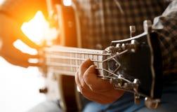 En man spelar på gitarren Arkivfoton