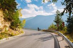 En man står bredvid en cykel på bergvägen Sommar i bergen av Bulgarien Royaltyfri Fotografi