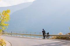 En man står bredvid en cykel på bergvägen Sommar i bergen av Bulgarien Arkivfoto