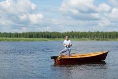 En man står i ett träfartyg i mitt av sjön och fisket för rotering royaltyfria bilder