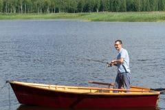 En man står i ett träfartyg i mitt av sjön och rotera en roterande rulle för att dra ut den fångade fisken royaltyfri bild