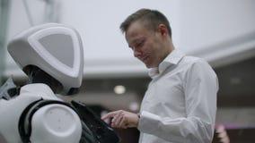 En man står med en robotbot och frågar honom frågor och frågar för hjälp, genom att klicka på skärmen på robotkroppen arkivfilmer