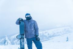 En man står med snowboarding ställningsmontering mansnowboard royaltyfria foton