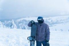 En man står med snowboarding ställningsmontering mansnowboard royaltyfri fotografi