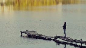 En man står på den gamla bron arkivfilmer