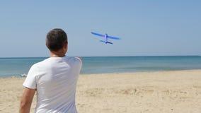 En man står på kusten på en varm solig dag och lanserar en ojämn nivå in i himlen En liten nivå flyger lager videofilmer
