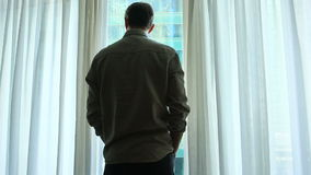 En man står vid fönstret med gardiner i ett hotellrum, ser ett fantastiskt stadslandskap stock video
